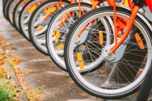 Row Of Colorful Bicycles For Rent At Municipal Bike Parking In Street