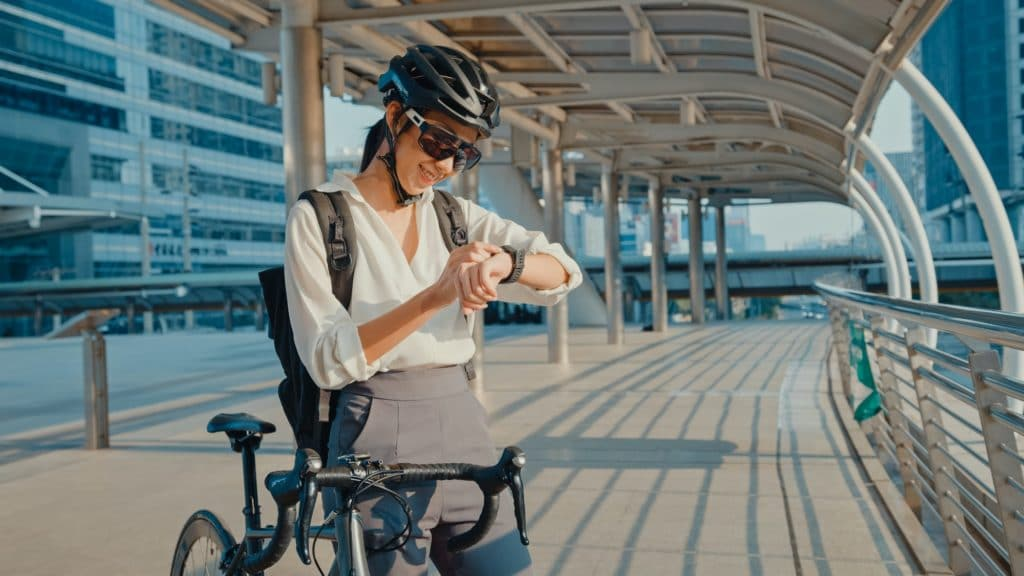 businesswoman with backpack bicycle smiling look smartwatch in city street go to work at office.