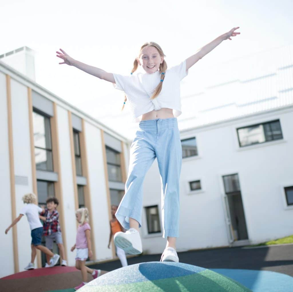 Cheerful schoolgirl playing outside on school break