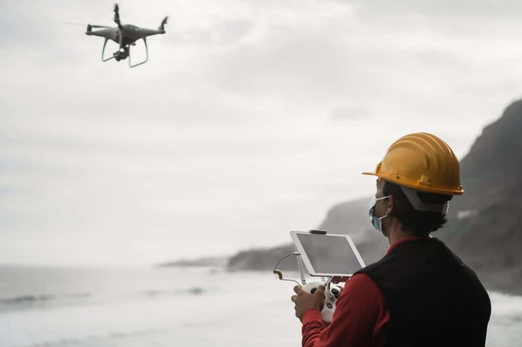 Man engineer flying drone while wearing protective mask - Focus on tablet