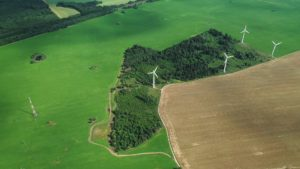 Windmills in summer in a green field.large windmills standing in a field near the forest.Europe