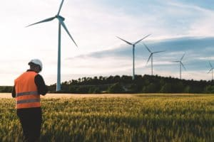 Engineer working at alternative renewable wind energy farm - Sustainable energy industry concept