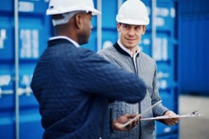 Freight manager talking with an engineer in a shipping yard