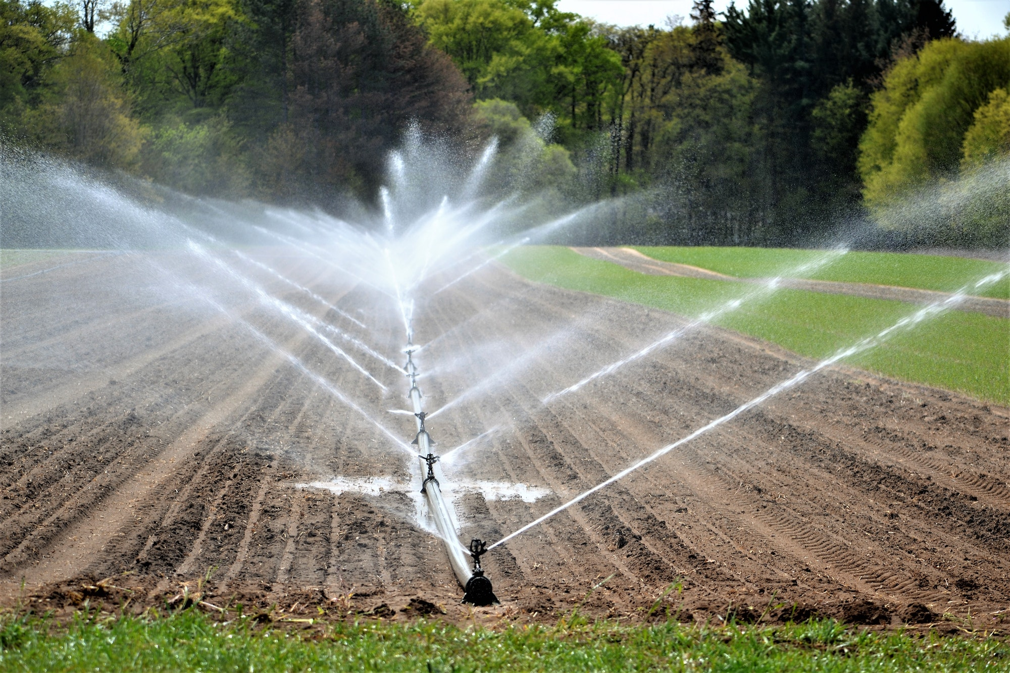 irrigation system watering crops farm land agriculture